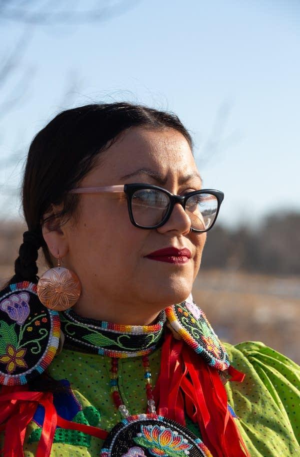 woman stands in profile wearing regalia