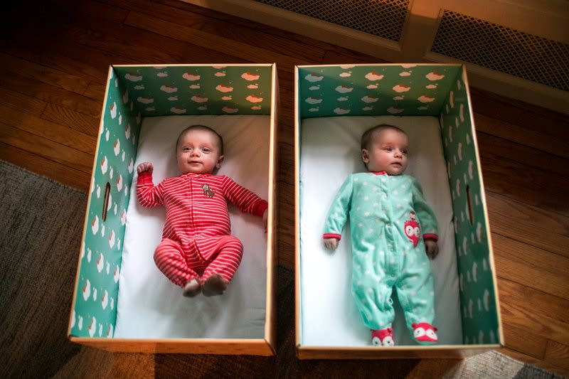 Twins Ryan and Nell Stimpert lie in their baby boxes