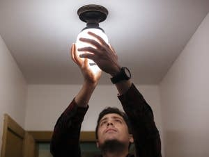 Andy Nail installs a high efficiency lightbulb.