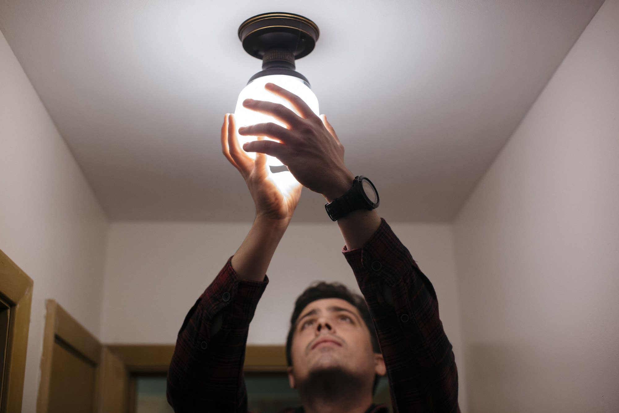 Andy Nail installs a high efficiency lightbulb.