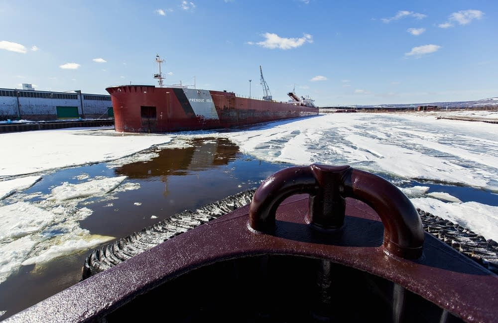 The tug Helen H breaks ice around freighters.