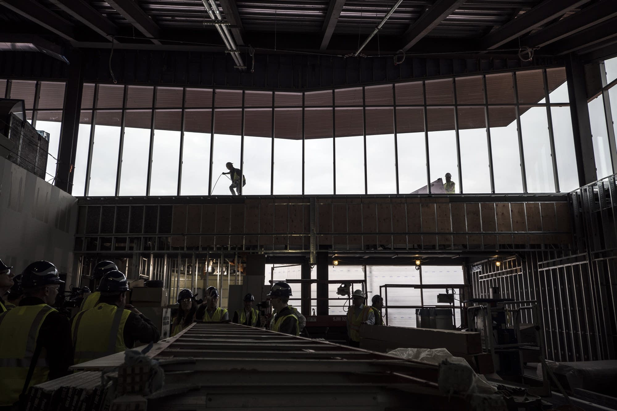 Workers are visible on the roof from the lobby that is under construction.