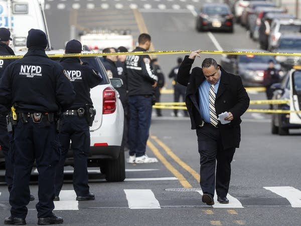 New York City police officers work the scene of a shooting