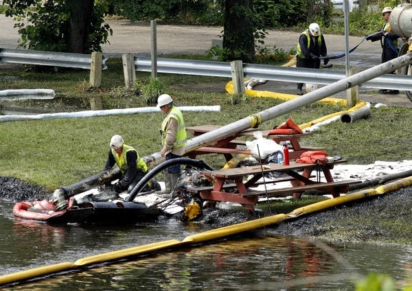 Workers using suction hoses try to clean up an oil spill.