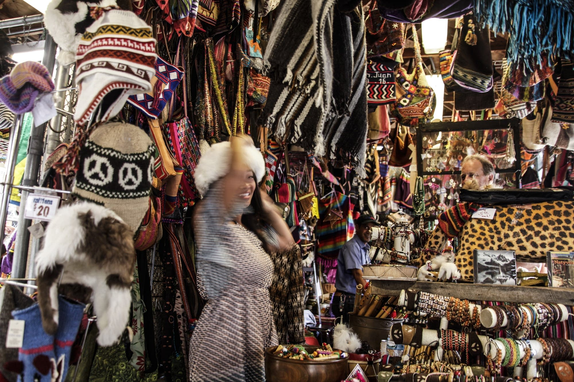 Inside a Bolivian merchandise store, a woman tries and alpaca hat.