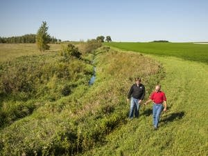 Jerry Jennissen inspects a county ditch with son in-law Lucas Sjostrom.