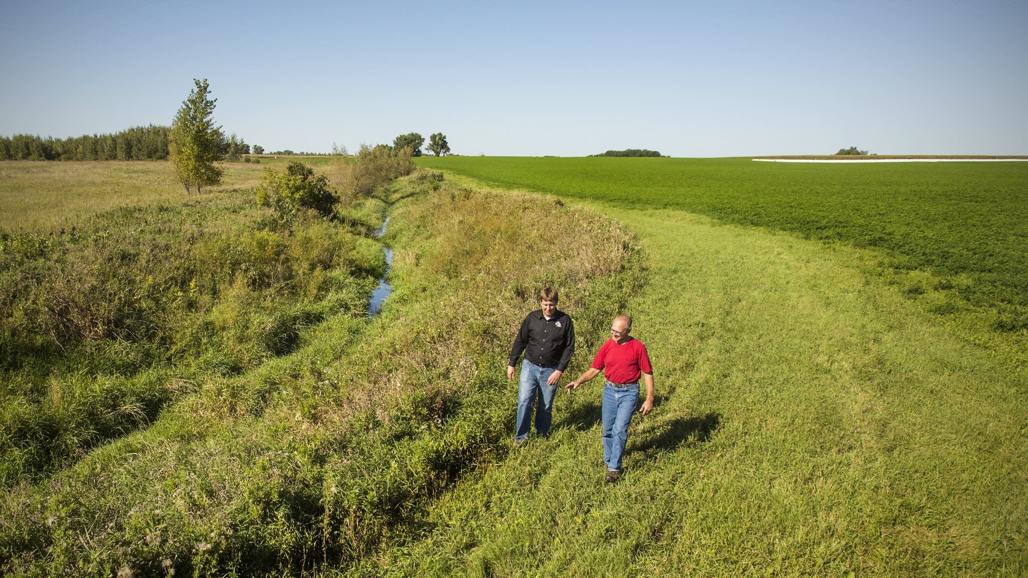 Jerry Jennissen inspects a county ditch with son-in-law Lucas Sjostrom.