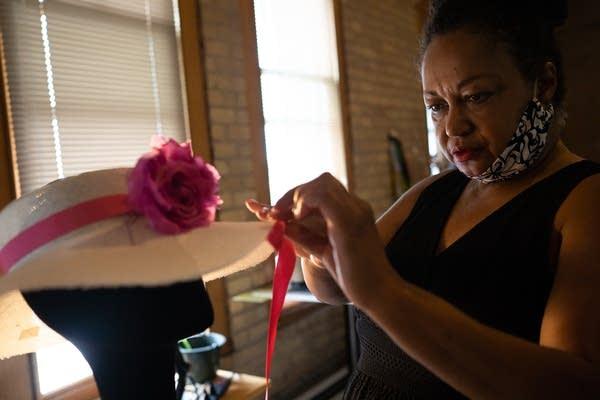 A woman wraps pink ribbon around a hat.