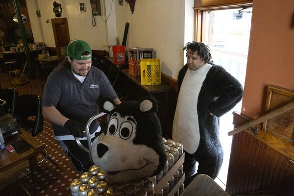 A man wearing a bear costume talks to a man delivering beer.