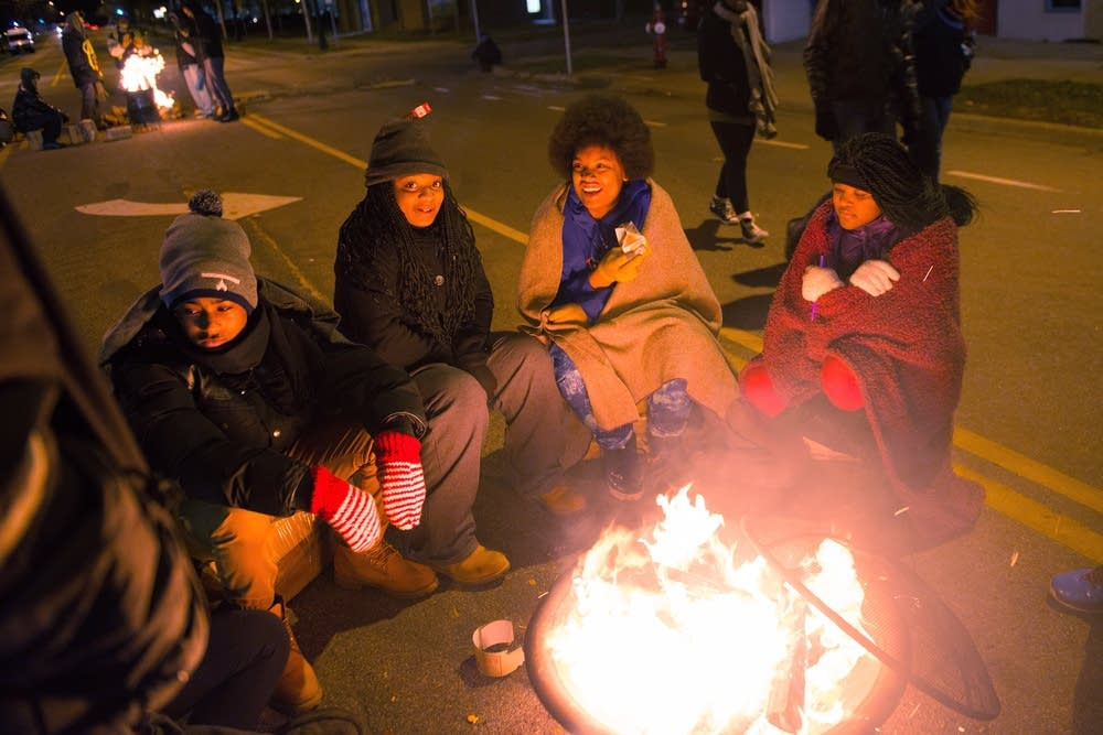 Protesters huddle around fires.