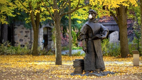 A face mask is placed on a statue of a man wearing robes and holding books