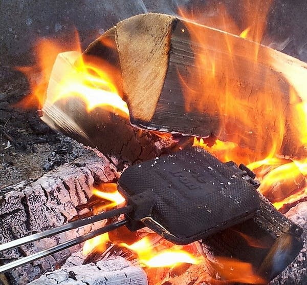 Cooking over the fire with a pie iron.