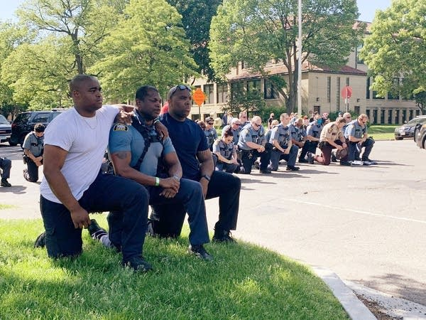 A number of St. Paul police officers kneeling