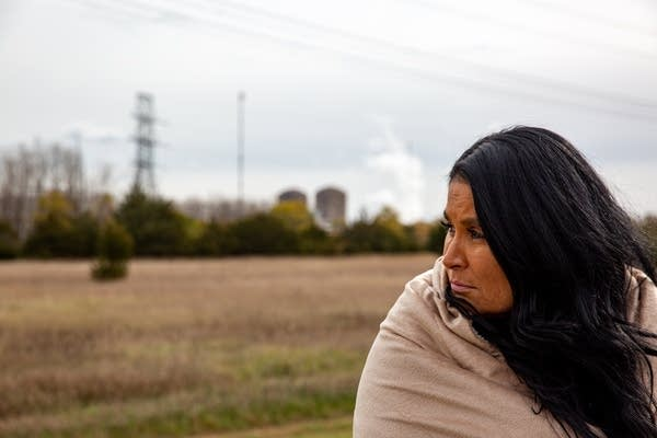 A woman gazes off to the left with a power plant behind her.