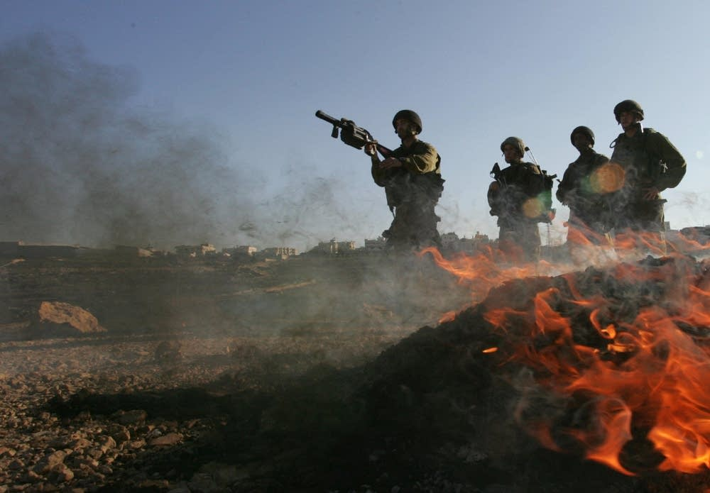 An Israeli soldier prepares to fire tear