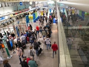 Travelers wait to get through security at the airport.