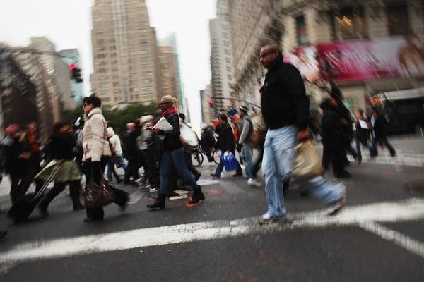 A crowd of people cross the street in New York.
