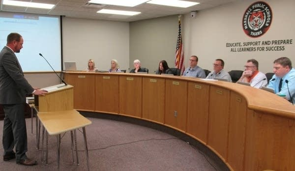 A speaker stands before a public school board meeting.