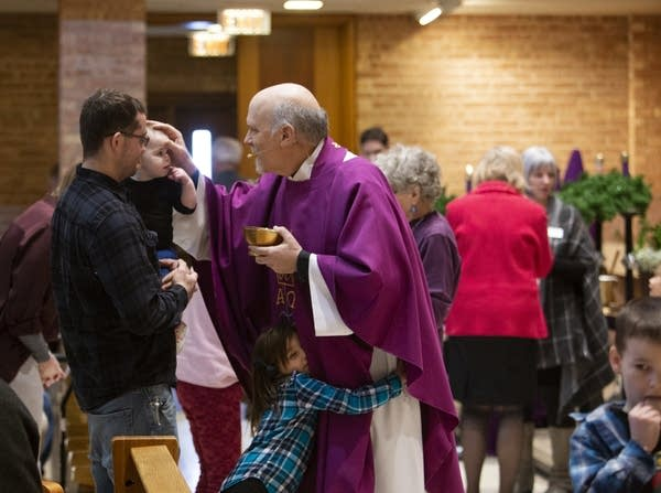 Father Paul of Saint Bridget's Saint Austin campus blesses Kyle Peltier.