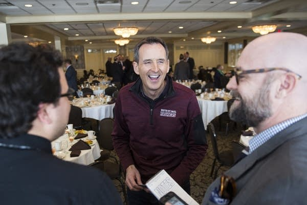 Tim Pawlenty laughs with reporters after giving a speech