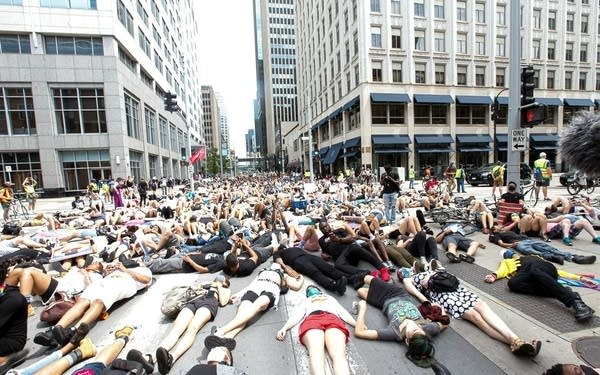 people lying on the road downtown in demonstration