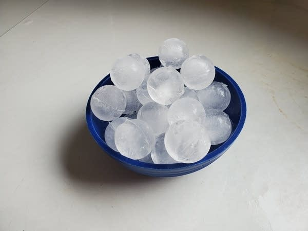"""Blue bowl containing small ice spheres or """"round ice cubes"""" if you like."""