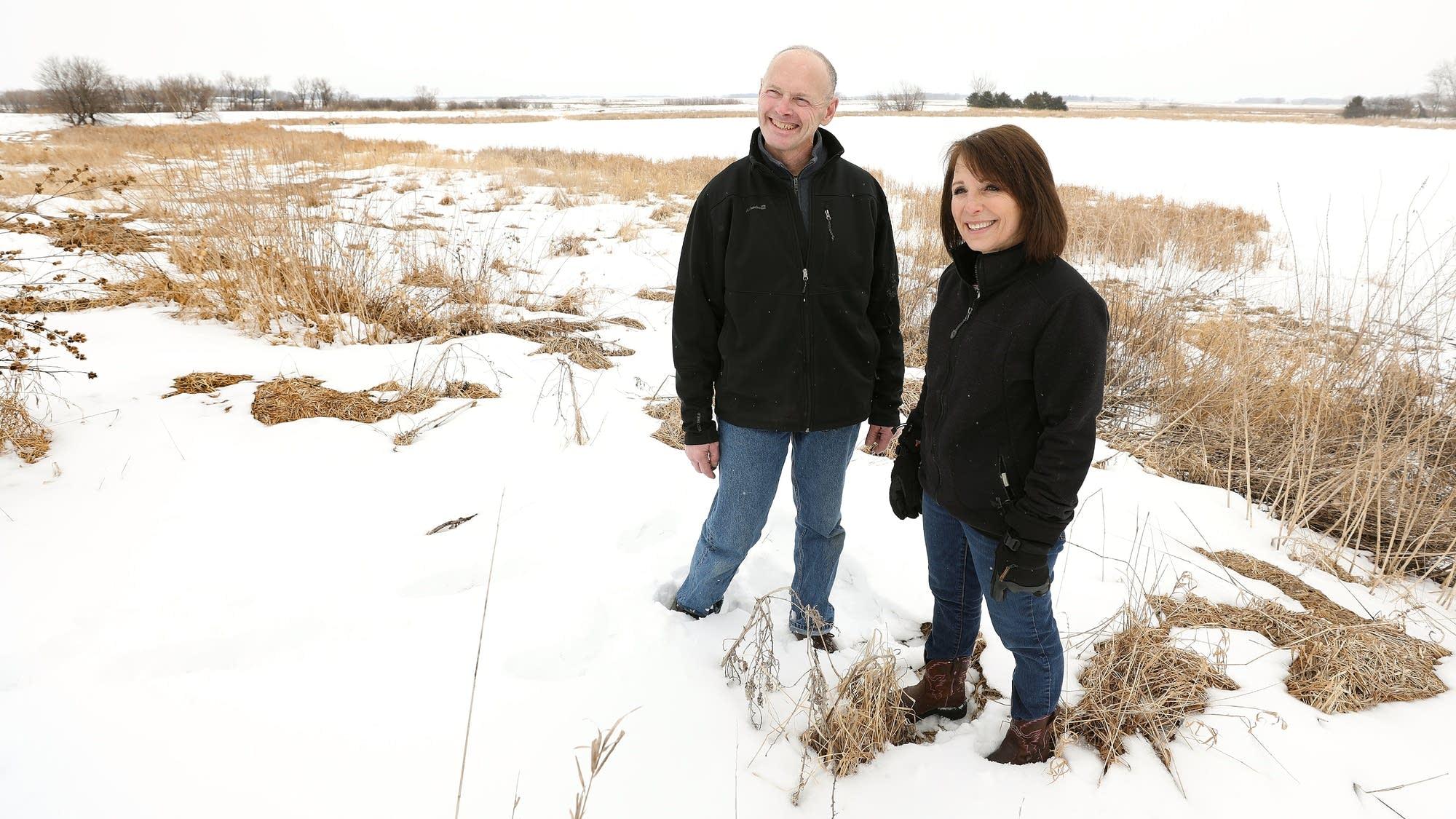 Jerry and Linda Jennissen stand along a natural buffer strip.