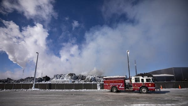 A firetruck in front of smoke billowing over a pile of ice-covered cars.