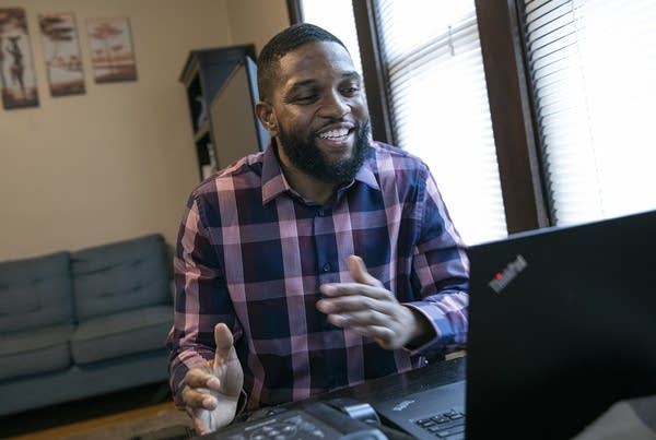 A man smiles as he gestures in front of a laptop.
