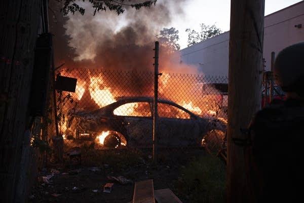 A car burns next to Lake Street