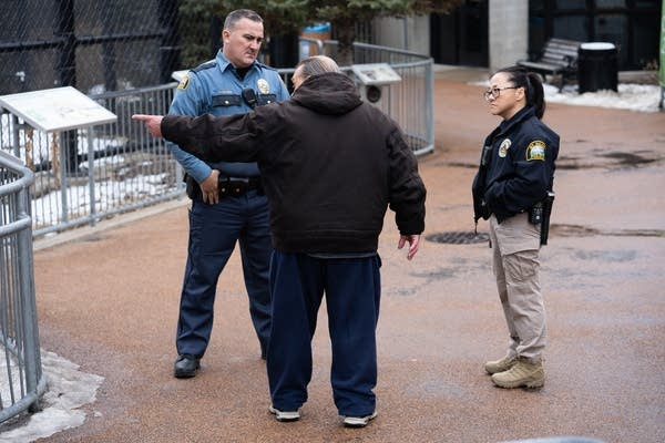 St. Paul police officers Matthew Arntzen and Lori Goulet talk to a man.