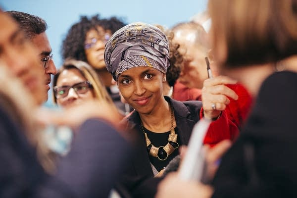 Rep. Ilhan Omar walks through a crowd at a press conference.