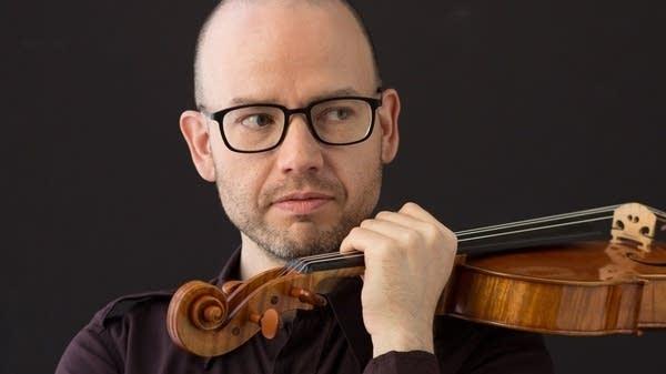 A bespectacled gentleman demonstrates improper violin technique