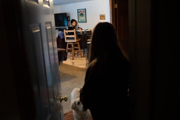 A woman looks through a door at a boy doing homework.