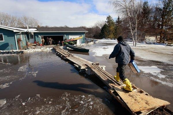 Russ Richards walks across a makeshift bridge