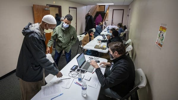 People fill out paperwork, wait at a walk-in vaccination clinic