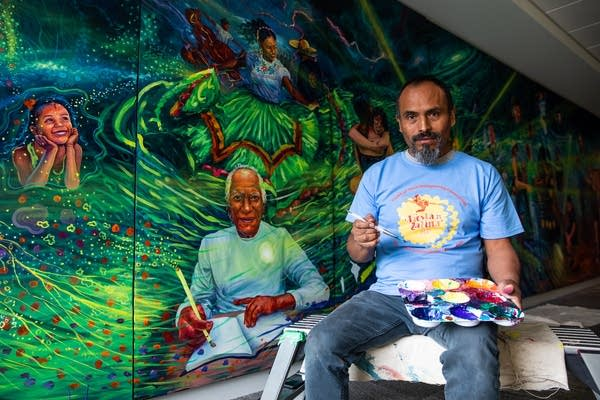 A man with a paintbrush sits in front of a large mural.