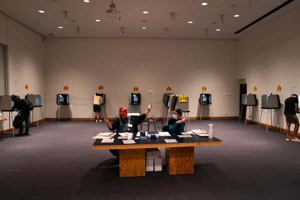 Two people sit in the middle of a room full of voting booths.