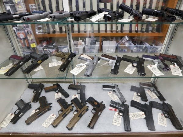 A display case shows a number of handguns.