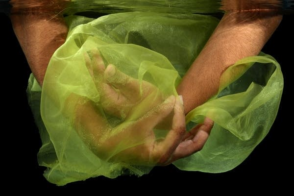 Photograph of two hands posed underwater with a green veil