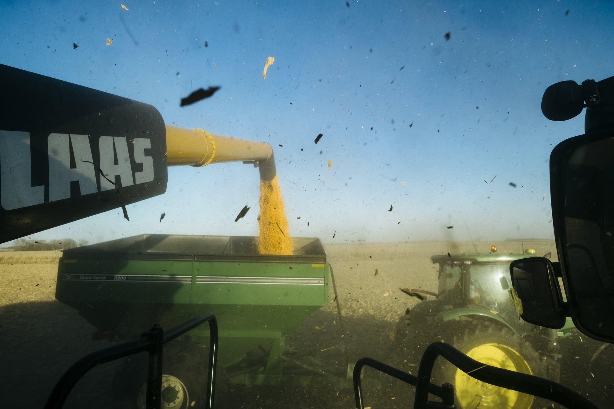 Debris flies through the air as corn is transferred to a tractor.