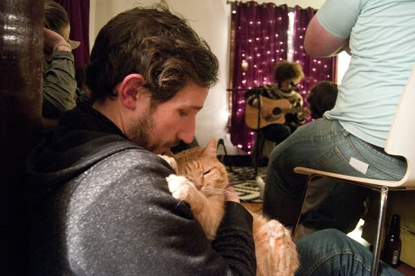Host Colin Scharf holds his cat during a concert.