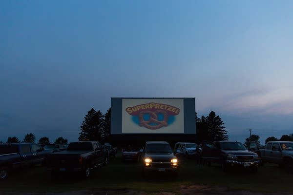 A dark sky with a film screen, and cars parked in front of the screen. One truck has its headlights on away from the screen.