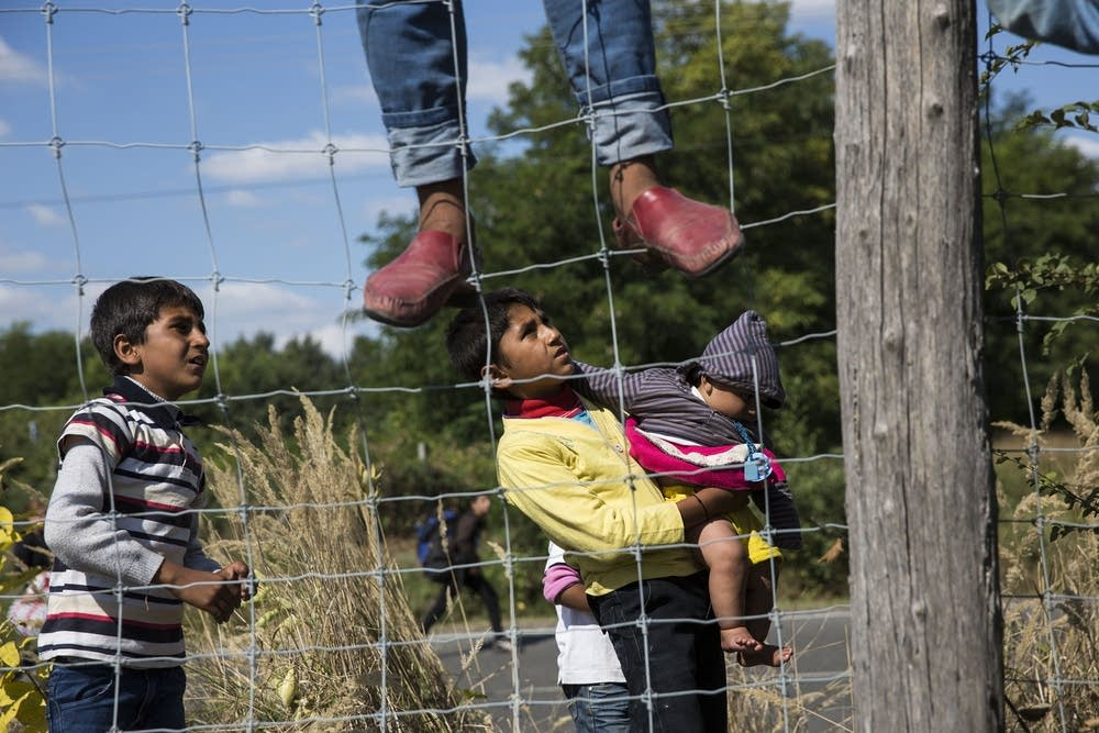 Syrian migrants climb over a fence