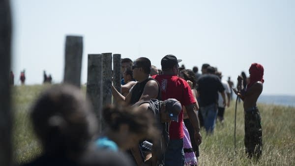 Protesters look over a fence at the construction.