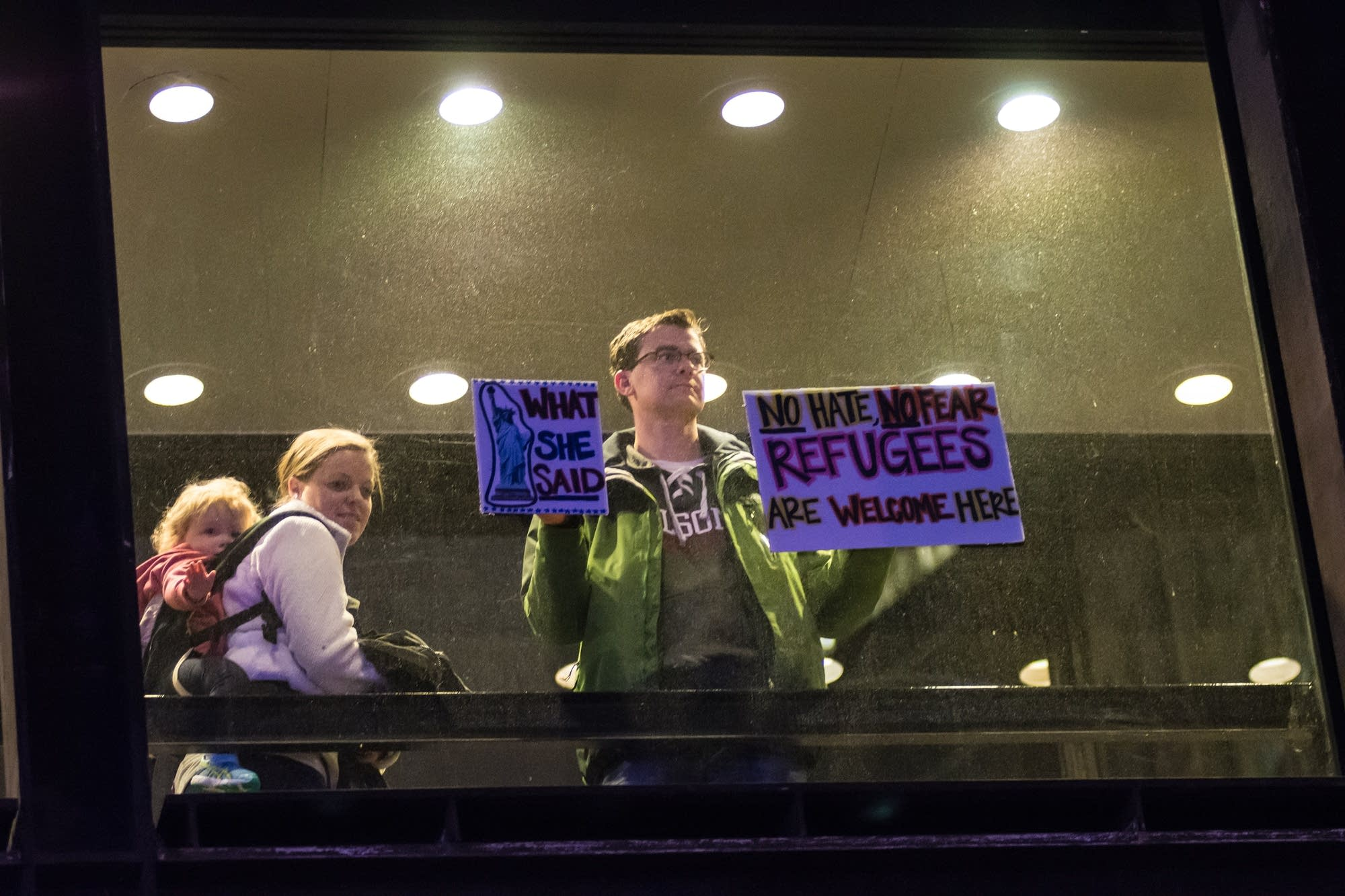 A man in a skyway holds up signs in support of protesters