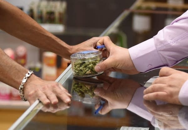 A budtender, right, shows cannabis buds to a customer.