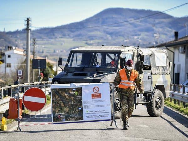 An Italian soldier blocks off a road