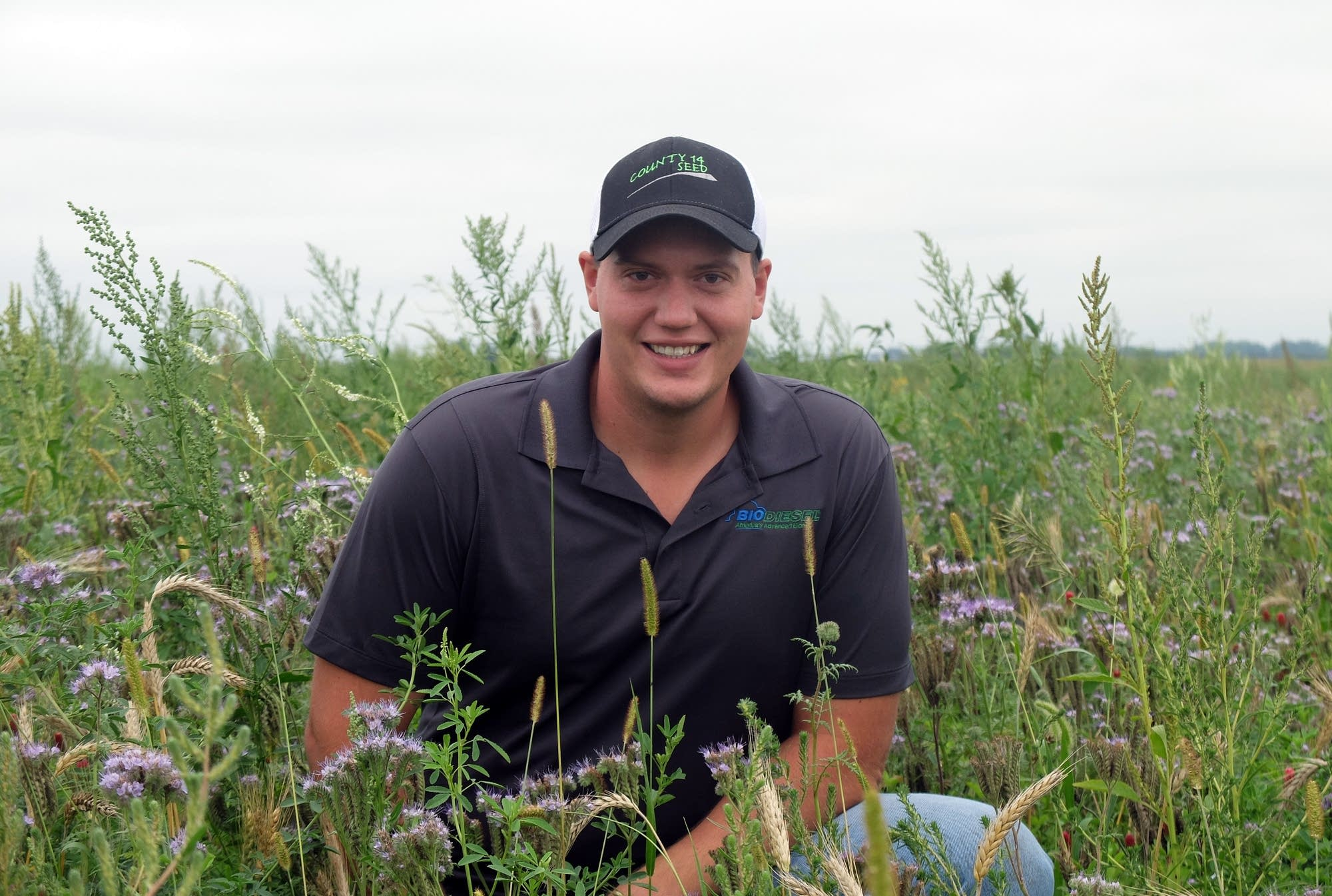 LaMoure, N.D., farmer Kasey Bitz poses in a field of pollinator habitat.