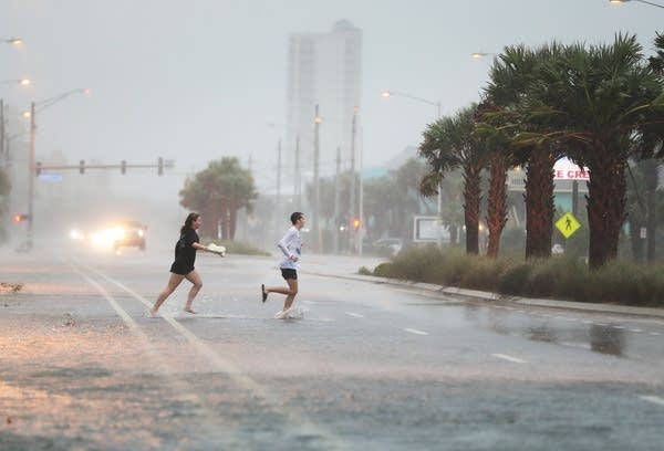 People run across a road through the rain.